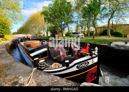 Traditional french barge in a lock on a sunny spring day on the Canal Du Midi  with the trees in full bloom, South of France - Stock Photo