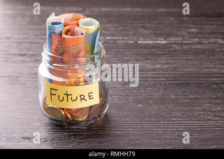 Glass jar with coins and Euro euro notes FUTURE inscription. On the old black table. The concept of financial savings for development