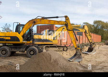 two yellow excavators parked at construction site - Stock Photo