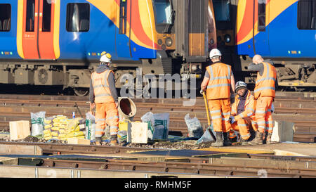 Clapham Junction, London, UK; 14th February 2019; Group of Rail Workers Working Trackside With Train Behind - Stock Photo
