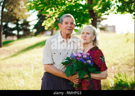 An elderly man of 80 years old gives flowers to his wife - Stock Photo