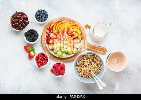 Raw vegan grain free paleo style granola or muesli made from nuts. Fruit berries platter, strawberries blueberries raspberries peach figs red currant, overhead view, selective focus - Stock Photo