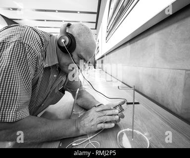 STRASBOURG, FRANCE - SEP 21, 2018: Apple Store with customers people buying admiring the new latest iPhone Xs and Xs Max preorder for Xr and Watch Series 4 wearable - black and white - Stock Photo