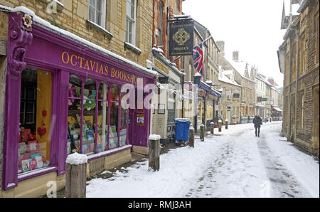 View up Black Jack Street, Octavias Bookshop, to Church of St. John Baptist, winter snow Cirencester town centre, Gloucestershire, England, GL7 2AA - Stock Photo
