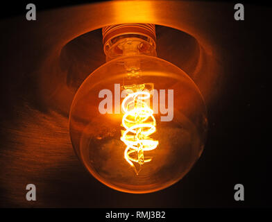 An incandescent electric light bulb, showing glowing filament, banned now in a number of countries, replaced with low energy and LED  bulbs - Stock Photo