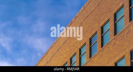 Brick building exterior against vivid blue sky - Stock Photo
