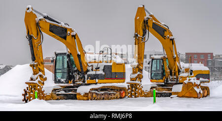 Excavators against snow and buildings in Daybreak - Stock Photo
