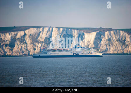 A ferry passing next to the white cliffs of Dover in the English Channel - Stock Photo