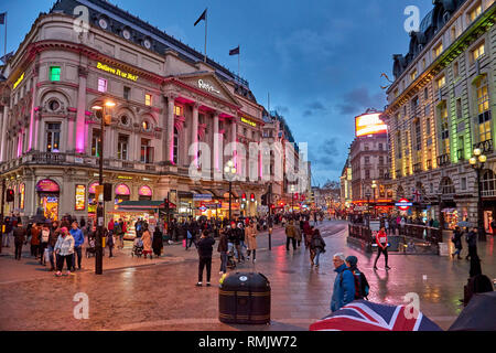 Rush hour and traffic near Piccadilly Circus with pedestrians walking in London's West End. Typical urban scenery in the center of London city. - Stock Photo