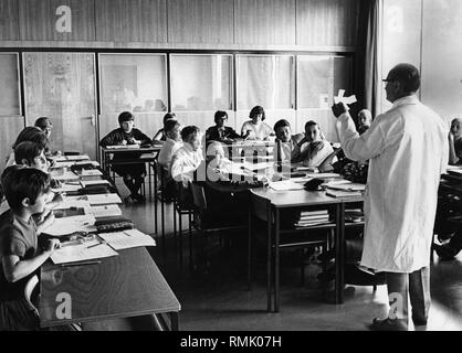 Children in school: Picture shows teacher with children of the Hauptschule (Secondary modern school) during a lesson. - Stock Photo