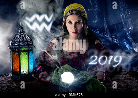 Psychic or fortune teller with crystal ball and horoscope zodiac sign of Aquarius - Stock Photo