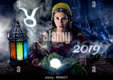 Psychic or fortune teller with crystal ball and horoscope zodiac sign of Taurus - Stock Photo