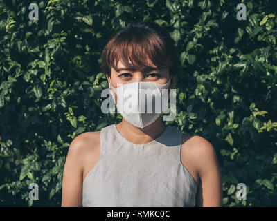 Beautiful asian woman wearing white protective N95 dust mask on green leaves background. Protection against pollution concept. - Stock Photo
