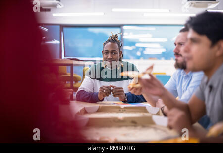 Friendly diverse multiethnic business team eating sharing pizza together in startup office, multiracial coworkers staff group enjoying break talking l - Stock Photo