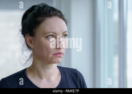 Thoughtful woman staring out of a window with a sombre deadpan expression in a head and shoulders portrait - Stock Photo