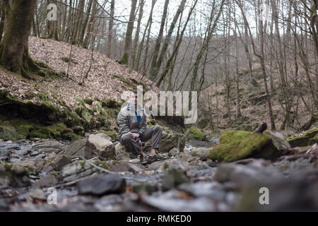 Young russian man hiking in Sochi National Park: resting sitting on a rock near the river - Stock Photo