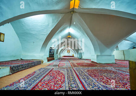 ISFAHAN, IRAN - OCTOBER 21, 2017: The shabestan (underground hall) of Jameh Mosque with white vault and colorful Persian carpets on the floor, on Octo - Stock Photo