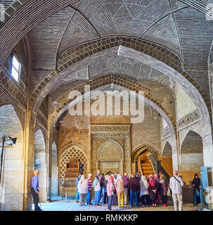 ISFAHAN, IRAN - OCTOBER 21, 2017: The group of tourists at the Uljayto mihrab in West hall of Jameh Mosque, on October 21 in Isfahan. - Stock Photo