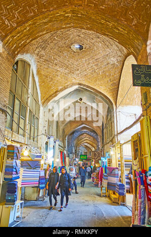 ISFAHAN, IRAN - OCTOBER 21, 2017: The narrow long corridor of textile department of Grand (Soltani) Bazaar with old brick vault and stalls on both sid - Stock Photo