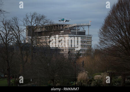 Seen from Ruskin Park in Lambeth south London, the Agusta-Westland AW-169 helicopter (G-KSSC) of the Kent Air Ambulance lifts off from the helipad of Kings College Hospital in Camberwell, on 11th February 2019, in London, England. - Stock Photo