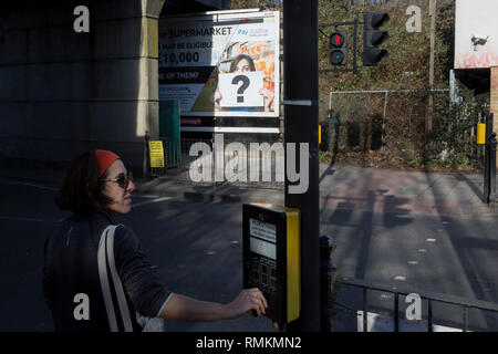 A lady presses the crossing signal in front of a question mark in the context of a billboard ad at East Dulwich, on 14th February 2019, in London, England. - Stock Photo