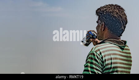 Middle Aged South Asian Man in his mid 50s wearing striped Tshirt, and in deep thinking, while enjoying his drink or beer from an aluminum can. - Stock Photo