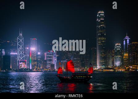 HONG KONG - DECEMBER 8, 2013: Illuminated Chinese red junk (Aqualuna) on Victoria Harbour, Hong Kong, on a foggy Winter night. - Stock Photo