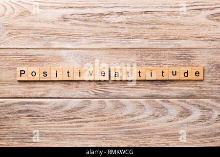 Positive Attitude word written on wood block. Positive Attitude text on wooden table for your desing, concept. - Stock Photo