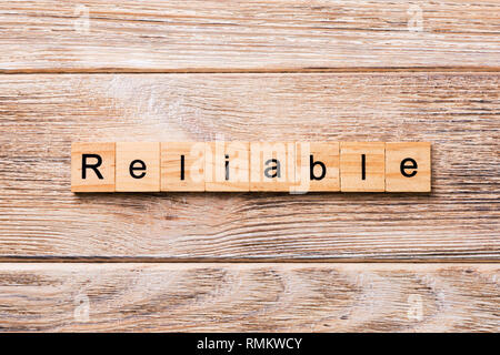 Reliable word written on wood block. Reliable text on wooden table for your desing, concept. - Stock Photo