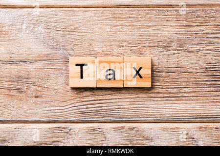 Tax word written on wood block. Tax text on wooden table for your desing, concept. - Stock Photo