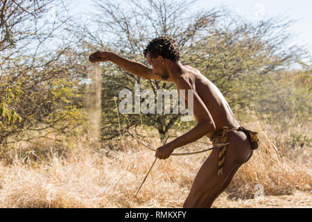 Bushman hunting with hand made Bow and Arrow. Photographed in Namibia - Stock Photo