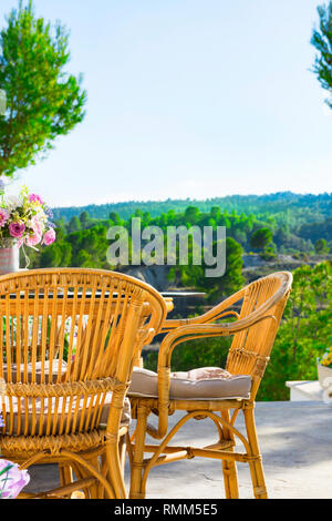 Terrace of luxurious white villa with wicker chairs table flowers bouquet on table fascinating view of valley mountains covered with green trees. Sunn - Stock Photo