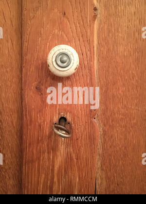 Old keyhole lock and knob in wooden cabinet door. Vintage furniture. - Stock Photo