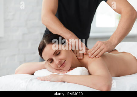 Young beautiful woman enjoying a back massage. Professional massage therapist is treating a female patient in apartment. Relaxation, beauty, body and  - Stock Photo