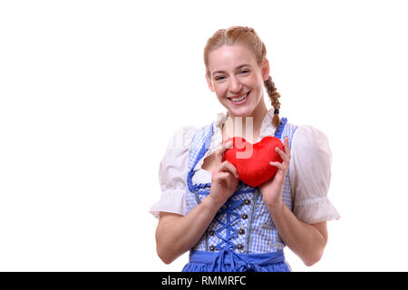 Studio shot portrait of a beautiful German young woman wearing traditional Bavarian dress for Oktoberfest while smiling and showing a red heart agains - Stock Photo