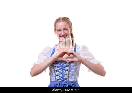 Studio shot portrait of a beautiful German young woman wearing traditional Bavarian dress for Oktoberfest while smiling and making a heart shape with  - Stock Photo