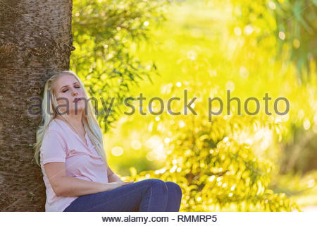 Pretty young woman leaning against a tree sleeping in a beautifully lit bright yellow background environment - Stock Photo