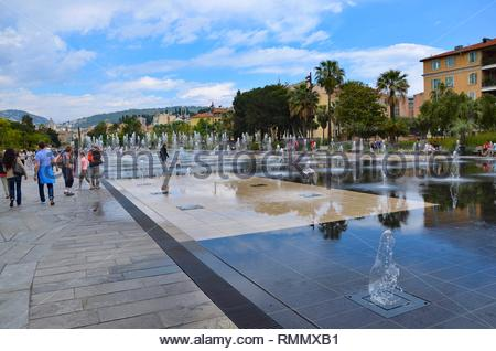 A public park called Promenade du Paillon in the city of Nice in South France, Cote d Azur, water fountains all over the place, buildings, palm trees - Stock Photo
