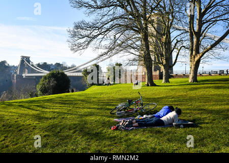 People relax on the grass beside Clifton suspension bridge, Bristol. Forecasters have predicted another day of warm weather on Friday after the unseasonably mild weather saw the warmest Valentine's Day in more than 20 years on Thursday with a maximum of 16.1C (61F) recorded in the Welsh town of Bala, Gwynedd. - Stock Photo