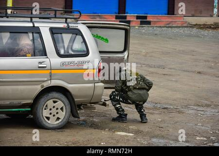 A paramilitary trooper seen inspecting a passenger vehicle close to the site of blast in Lethpora, about 28 kms from Srinagar, Indian administered Kashmir.  At least 49 paramilitary troopers were killed in one of the deadliest militant attacks in Kashmir when a  suicide bomber rammed his explosive-laden car into a Central Reserve Police Force (CRPF) convoy. Jaish-e-Muhammad militant group had claimed the responsibility for the attack. - Stock Photo