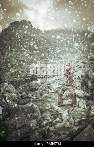 man with gun and gas mask in mountainous place - Stock Photo
