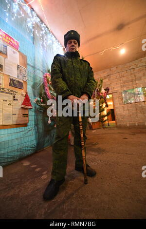 DPR soldier from the Shakhtyorsk division, called name, Arkadiy, seen relaxing between shifts in the division HQ. The war between the Ukrainian army and the soldiers of the Donetsk Peoples Republic has cost the lives of 12,000 people and those who have been displaced exceed a million. It escalated in 2014. Despite a ceasefire in place, it is evident that death still occurs from predominantly, sniper, mortar and mines. The construction of trenches either side of no-man's land, (often only 100mt apart) have ensured a static yet aggressive confrontation. The Minsk ceasefire agreement and constant - Stock Photo