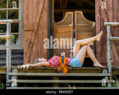 Pretty teen girl with violin musical instrument lying on back on porch of Western style saloon entrance wooden doors - Stock Photo