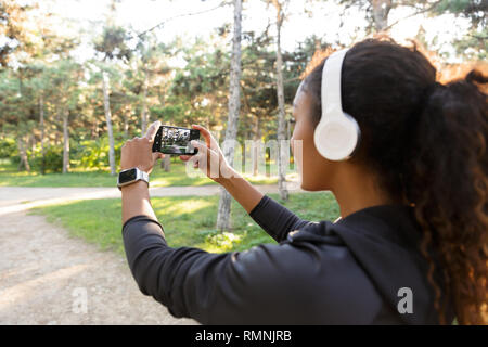 Portrait of african american woman 20s wearing black tracksuit and headphones taking selfie photo on cell phone while walking through green park - Stock Photo
