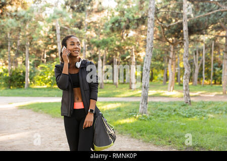 Image of sporty woman 20s wearing black tracksuit and headphones speaking on mobile phone while walking through green park - Stock Photo