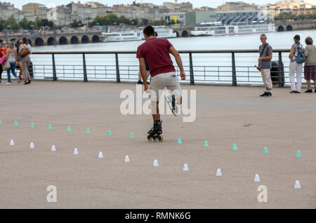 Bordeaux, France - September 9, 2018: Roller skater performs acrobatics in Quai Lousi XVIII in Bordeaux, France - Stock Photo