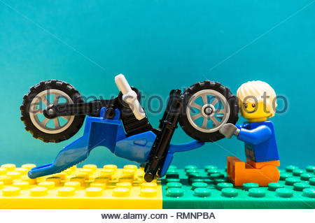 Poznan, Poland - February 13, 2019: Lego toy man character trying to fox a wheel on a motorbike. The vehicle needed some maintenance. - Stock Photo