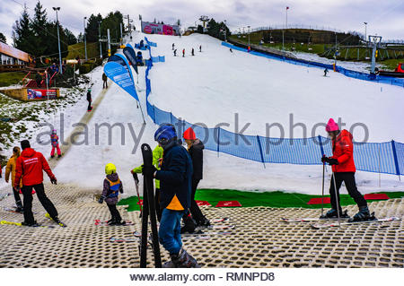 Poznan, Poland - February 10, 2019: Kids and instructors waiting in a line to climb up the ski training track at the Malta park on a cold winter day w - Stock Photo
