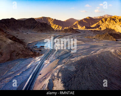 Desert road surrounded by sandstone rocks aerial view - Stock Photo
