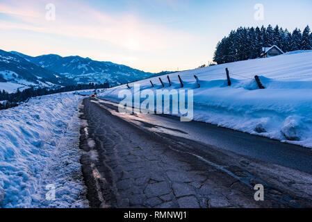 Empty, asphalt, destroyed road in winter. Big snow around. Birnberg, Schladming-Dachstein, Dachstein massif, Liezen District, Styria, Austria, Europe - Stock Photo